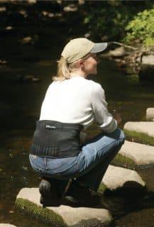 Woman crouching while wearing a back brace