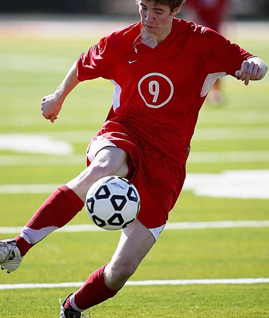 A soccer player controlling the ball. The athletically demanding nature of the sport makes soccer injuries an all too frequent occurrence.