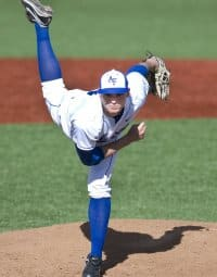 Baseball pitcher in the follow through stage of throwing a pitch. Pitch and throwing the baseball are among the leading contributors to shoulder problems that may require wearing shoulder supports for baseball injuries.