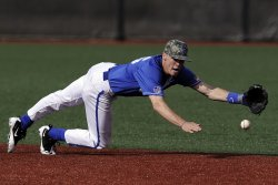 Baseball outfielder lunging for the ball with his ankle in a twisted position. In this situation adhesive tape for a baseball player can play a useful role in supporting his ankles