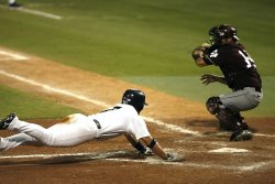 Baseball batter diving for the plate. Actions like this can cause overuse injuries that can be addressed by wearing kinesiology tape for baseball activity.
