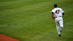 Baseball player running in the outfield. Extensive running can produce ankle injuries and result in the need to wear an ankle brace for baseball games or practice.
