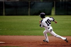 Baseball batter rounding the bases. Rounding the bases can place stress on the knees and result in a need to wear knee braces for baseball games or practice.