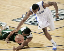 Basketball player sprinting off balance with the ball after dispossessing another player. The need to accelerate sharply in situations like this can result in shin splints and lead to the use of shin supports for basketball injuries.