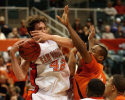 Basketball player holding up his hands to block his opponent's shot. Using mouthguards for basketball can prevent dental injuries caused by contact with other players' hands.