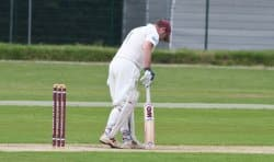 A batsman at the crease patting the wicket. Some elbow problems can befall batsmen who use the incorrect grip size and may need to start wearing an elbow brace for cricket games or practice.