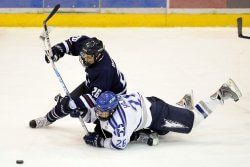 Two Hockey Players Competing For The Puck. The consequences of falling on the shoulder as one of the players has in this image can include shoulder injuries treatable by wearing a shoulder support for hockey.