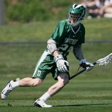 A lacrosse player on the field. Lacrosse players sometimes need shin supports to help treat injuries like shin splints.