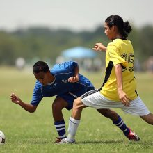 Soccer player falling down after being tackled. Falls like thi can sometimes result in wrist injuries for soccer players, some of which can be treated using a wrist brace.