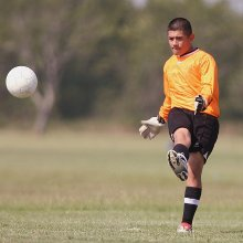 Soccer player kicking the ball. ACL and MCL knee injuries are common in soccer and may be treated using knee braces.