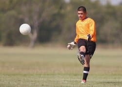 Soccer player kicking the ball. ACL and Meniscus Tear knee injuries are common in soccer and may be treated using knee braces.