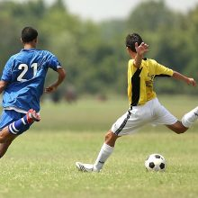 A soccer player taking a shot while being challenged by an opponent. Soccer players can suffer from a number of hip & groin injuries which may require treatment using a hip or groin support.
