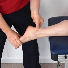 Therapist treating a patient with an ankle sprain. Seeking professional help is one of the key steps to coping with injury recovery setbacks.