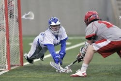 Two lacrosse players competing for the ball. A back brace can sometimes be required to treat lacrosse related low back pain.