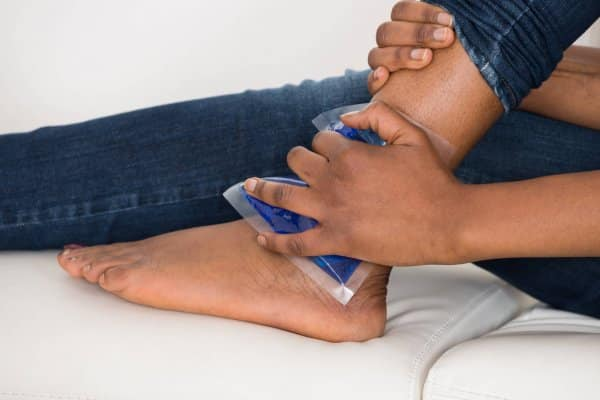 Person Applying A Cold Compress To Treat A Sprained Ankle