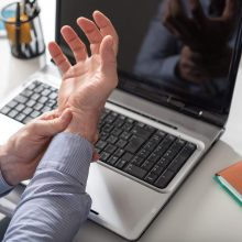 Businessman suffering from wrist pain due to carpal tunnel syndrome