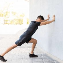 A man performing a wall stretch - one of the most effective plantar fasciitis exercises