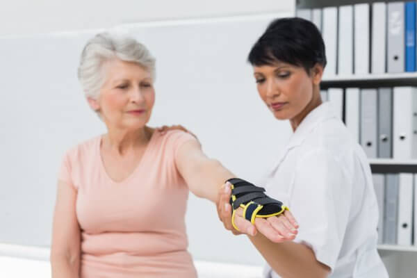 Elderly woman being fitted with a wrist brace by a healthcare professional