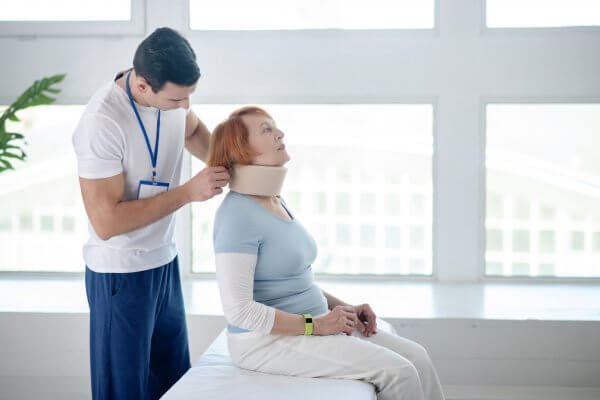 Neck collar. Pleasant aged woman wearing a cervical collar or neck brace while undergoing medical therapy