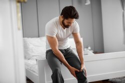 """Portrait of unhappy handsome muscular bearded man having knee pain and sitting on the edge of the bed at home holding his knee and probably asking """" how does a knee brace help with knee pain ?""""."""