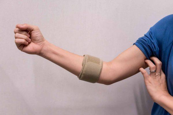 Woman wearing an elbow brace to reduce pain