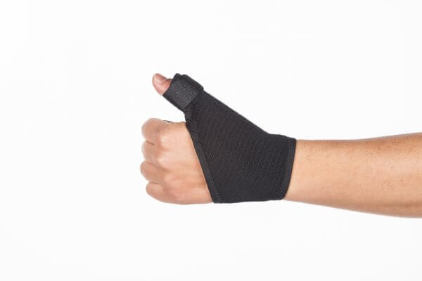 A thumb brace worn on the left hand