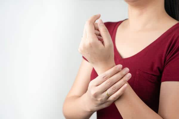 A young woman holding her wrist due to a sprain, arthritis or other injury.