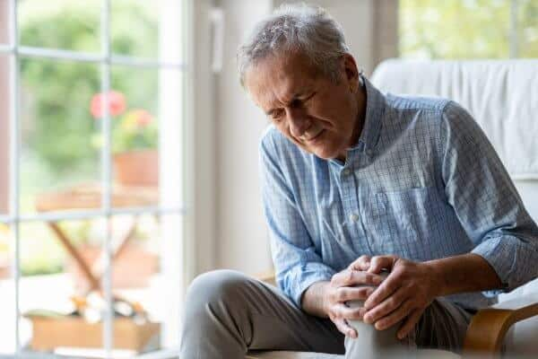 Senior man with knee pain and holding his knee.