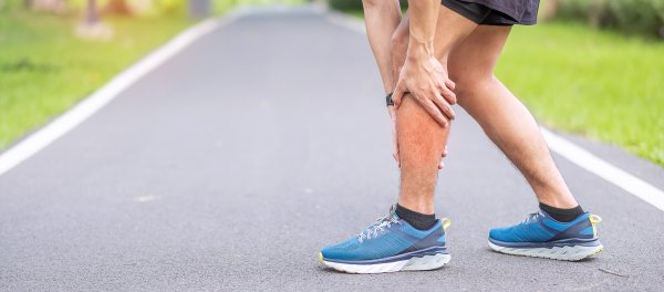 Man holding his lower leg, possibly experiencing shin splint pain