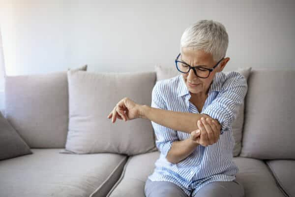 Old woman hand holding her elbow suffering from elbow pain, possibly due to arthritis.