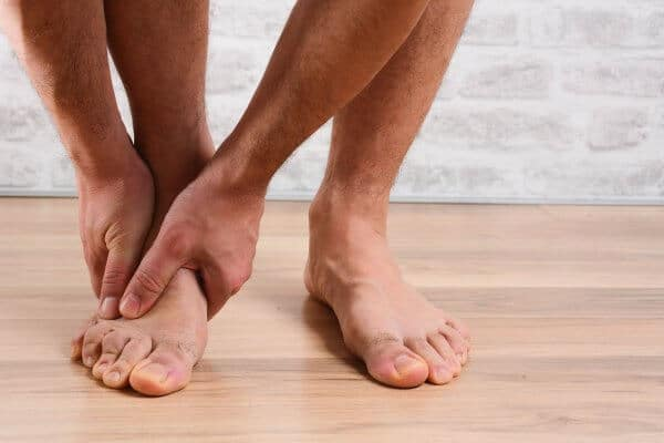 Man holding his foot and possibly experiencing pain in the arch of the foot
