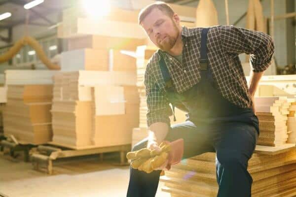 Tired handsome bearded manual worker with closed eyes sitting on stack of wooden plank and massaging lower back while feeling pain in lower back