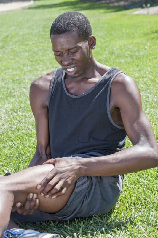 Young lean African American male athlete sits on grass clutching injured leg and hamstring while in excruciating pain, possibly with thigh strain injury