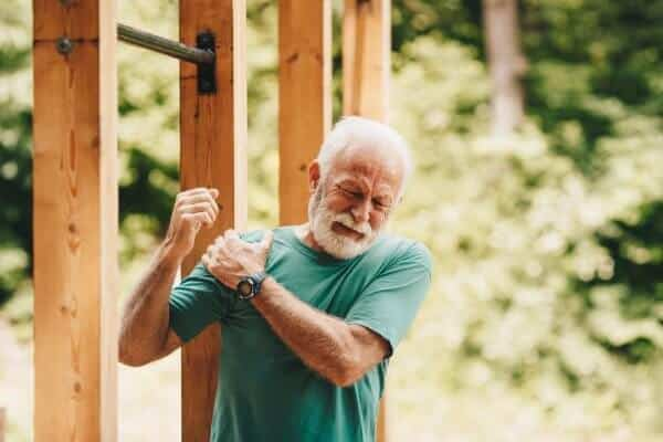 Senior man suffering with shoulder pain, possibly tendonitis, during workout