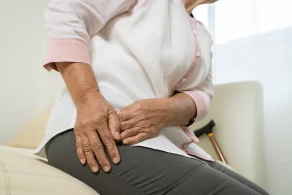 Elderly woman suffering from hip pain at home.