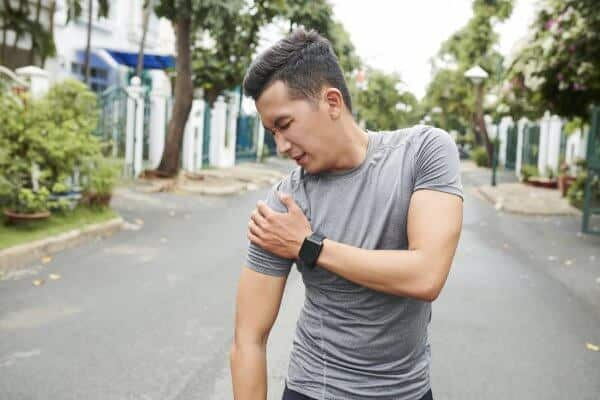 Young Asian man with pain from dislocated shoulder when training outdoors