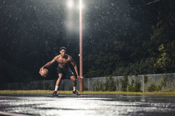 Young man playing basketball under lights. Ankle braces have been found to work to reduce the risk of ankle sprains among high school basketball players